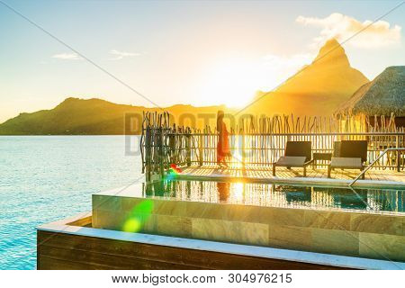Luxury resort high end hotel rich people lifestyle woman tourist relaxing watching sunset on private balcony terrace of overwater bungalow suite in Bora Bora, Tahiti, French Polynesia.