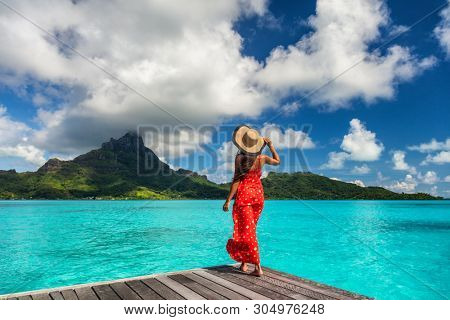 Bora Bora island luxury resort hotel woman relaxing at view of Mt Otemanu in Tahiti, French Polynesia Honeymoon travel destination for summer vacation.