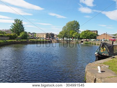 A View Of The Lock Entrance To Brighouse Basin With Moored Houseboats On The Calder And Hebble Navig