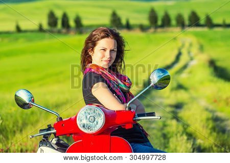 Portrait of young beautiful woman with a scooter and tuscany landscape in background