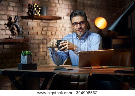 Businessman working at desk in loft office using tablet computer.