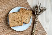 Two Slices of Toast Bread and Ear of Wheat on a Wooden Table Setup poster