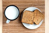 Two Slices of Toast Bread and Tin Mug of Milk on a Wooden Table Setup poster