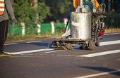Thermoplastic spray marking machine during road construction. Worker painting white line on the street surface (Road worker painting) poster