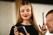 Woman Hairdresser Looking at Client Mobile Phone. Young Hairstylist Holding Comb and Scissors in Hands. Male Customer Showing Haircut to Stylist. Beautiful Stylist with Hairbrush in Beauty Salon poster