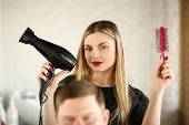 Blonde Hairstylist Showing Blow Dryer and Comb. Woman Hairstylist Using Hairbrush and Hairdryer for Styling Male Haircut in Beauty Salon. Female Stylist Making Hairdo for Client Looking at Camera Shot poster