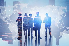 Diverse Team Of Business People Standing Over Night Cityscape Background With World Map. Concept Of