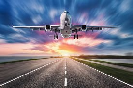 Airplane And Road With Motion Blur Effect At Sunset. Landscape With Passenger Airplane Is Flying Ove