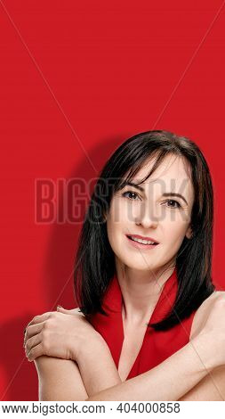 Attractive Brunette With Bright Shawl On Neck Posing On Red Background