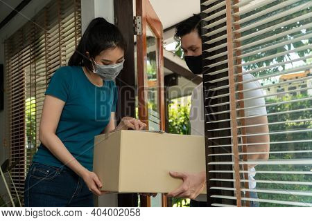Asian Man Wearing A Protective Mask And Delivering Packages From Grocery After Online Order. Woman A