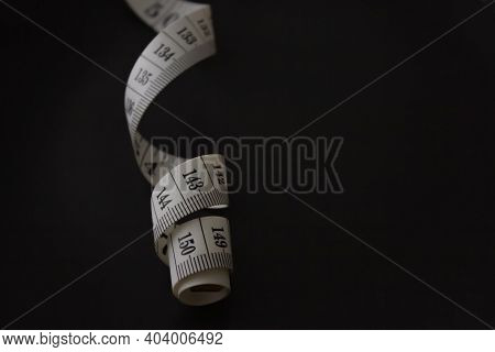 White Measuring Tape On Black Background, Shallow Depth Of Field. Slimming Measuring Tape. Space For