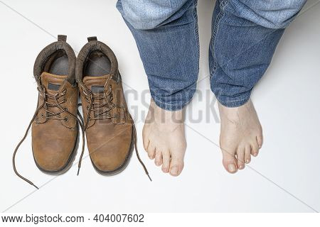 A Pair Of Shoes And A Man With Bare Feet