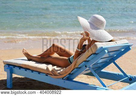 Beautiful Woman Sunbathing On A Beach At Tropical Travel Resort, Enjoying Summer Holidays. Girl Hold