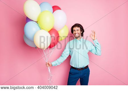 Photo Portrait Of Winking Man Showing Ok-sign Holding Helium Balloons Isolated On Pastel Pink Colore