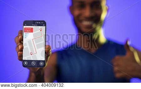 African Fitness Guy Showing Smartphone With Step Counter App Standing Posing Over Blue Studio Backgr