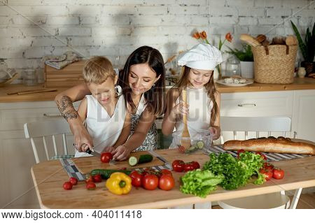 Mom Cooks Lunch With The Kids. A Woman Teaches Her Daughter To Cook From Her Son. Vegetarianism And