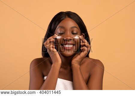 Closeup Of Pretty Young Black Lady With Closed Eyes Applying Hydrogel Eye Patches Over Beige Studio