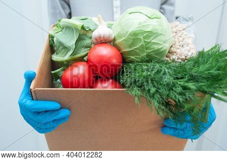 Volunteer In Gloves Holds Food Donation Box Vegetables To Help The Sick Or Poor. Donat Box With Food