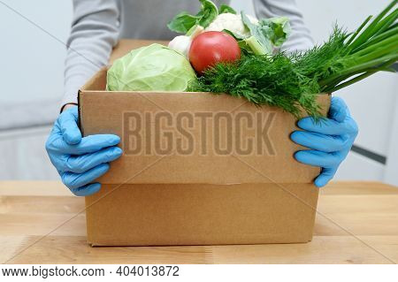 Volunteer In Gloves Holds Food Donation Box Vegetables To Help The Poor. Donat Box With Foodstuffs