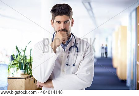 Portrait Of Thinking Male Doctor Standing On Hospital's Foyer.