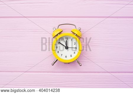 Yellow Old Style Alarm Clock On Pink Wooden Background With Place For Your Text. Copyspace Time Conc
