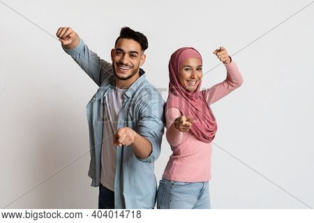 Gotcha. Cheerful Muslim Couple Pointing Fingers At Camera, Indicating Somebody, Happy Arab Man And W