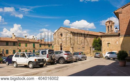 Monticiano, Italy - September 7th 2020. Cars park in front of the Parish Church in the historic centre of the medieval town of Monticiano in Siena Province, Tuscany, Italy. The church is know as Parrocchia e Chiesa di Santi Giusto e Clemente