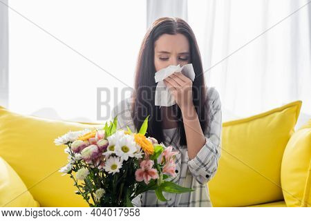 Allergic Woman Wiping Nose With Paper Napkin While Sitting Near Flowers