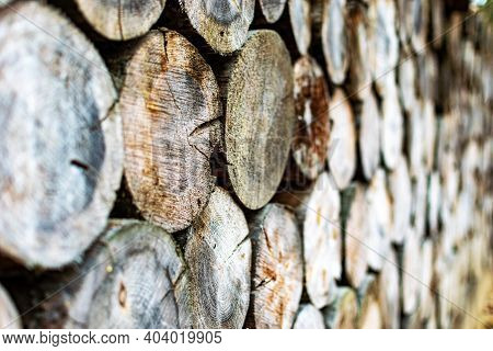 Wooden Logs In A Pile With Bokeh. The Firewood Is Stacked.