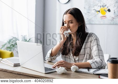 Allergic Woman Wiping Nose With Paper Napkin While Working At Laptop On Blurred Foreground