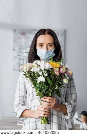 Allergic Woman In Medical Mask Looking At Camera While Holding Flowers