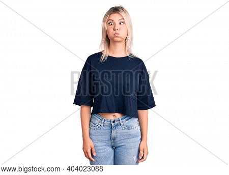 Young beautiful blonde woman wearing casual t-shirt puffing cheeks with funny face. mouth inflated with air, crazy expression.