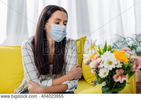 Sad Allergic Woman In Medical Mask Sitting Near Flowers At Home