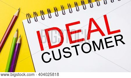 Ideal Customer On A White Notepad With Pencils On A Yellow Background. Business Concept