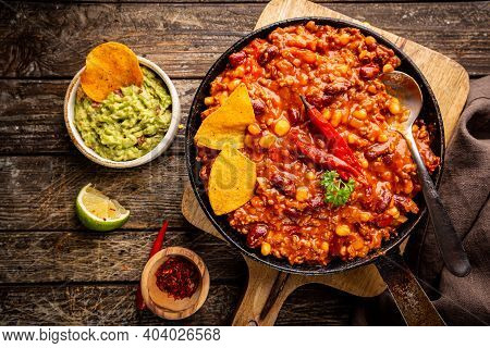 Mexican Hot Chili Con Carne In A Pan With Tortilla Chips On Dark Background, Top View