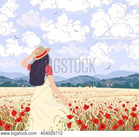 Young Woman Enjoys The Wheat Field Scenery. Dreamy Girl In Straw Hat Walking Among Ripe Wheat Ears A