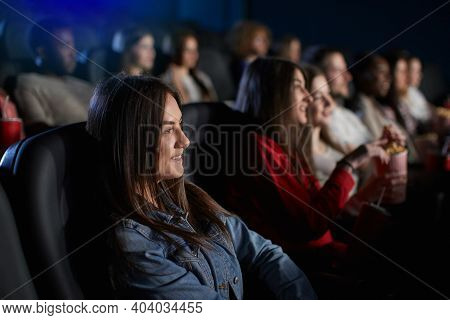 Side View Of Young Stunning Brunette Girl Watching Movie In Cinema, Wearing Casual Outfit. Selective