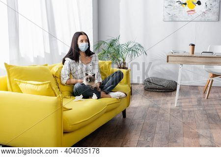 Allergic Woman In Medical Mask Sitting With Cat On Yellow Sofa