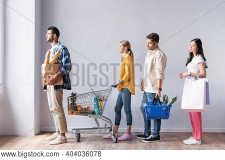 Multiethnic People With Shopping Basket, Cart And Bags Waiting In Queue In Market