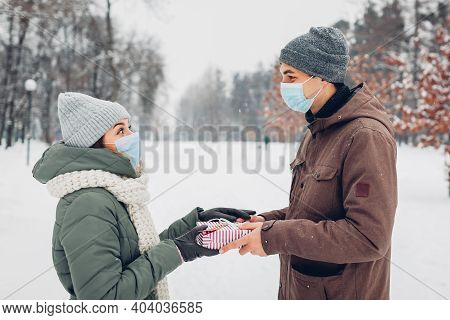 Man Gives Gift Box To His Girlfriend For Valentines Day In Snowy Winter Park. Couple Wear Masks. Cor