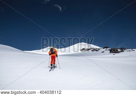 A Mountaineer Skier With A Backpack, An Ice Ax, Skis And Poles, Ascend On A Ski Tour To Mount Elbrus