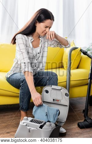 Young Allergic Woman Wiping Nose While Holding Vacuum Cleaner Dust Bag