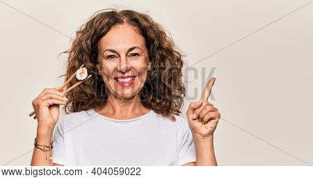 Middle age beautiful  woman eating sushi using wooden chopsticks over white background smiling happy pointing with hand and finger to the side