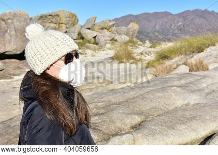 Woman With Covid-19 Black Face Mask On A Beach In Winter With Black Coat, Sunglasses And White Wool