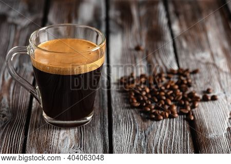 Espresso Coffee In A Glass Cup On A Dark Rustic Wooden Table. Creamed Coffee And Roasted Coffee Bean