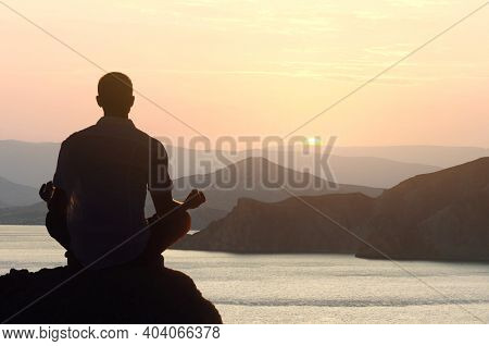Silhouette of a man meditating yoga at dawn in a lotus position by the sea