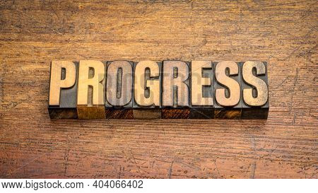 progress word abstract in vintage letterpress wood type against weathered wooden background, advance and development concept