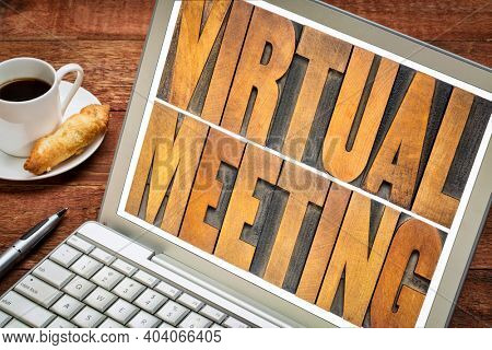 virtual meeting word abstract in vintage letterpress wood type on a laptop screen, working from home, networking and telecommunication concept
