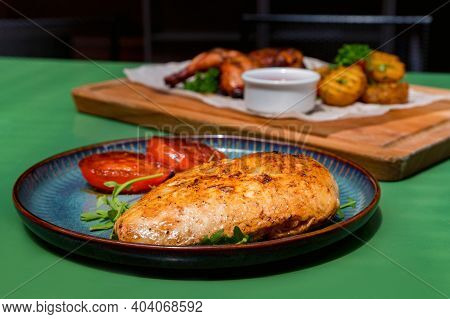 Close View Meal With Boneless Skinless Chicken Breast, And Fried Tomatoes.