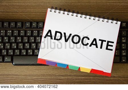 The Word Advocate Is Written On A White Notepad That Lies On The Computer Keyboard